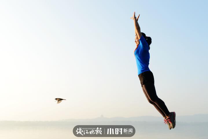 """13、我也""""飞""""一个:杭州西湖边,一位女士腾空跳起,她的身后刚好一只鸟儿飞过。戴文昌 摄.jpg"""