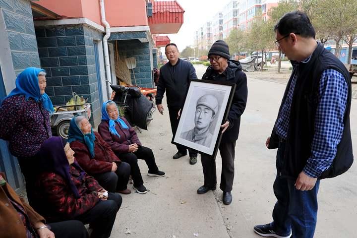 1、手捧父亲画像回家,陈恒月开心地向村里老人们展示着画像。.jpg