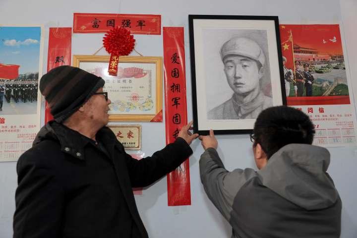 4、一家人把烈士画像悬挂在了光荣之家荣誉栏里。.jpg