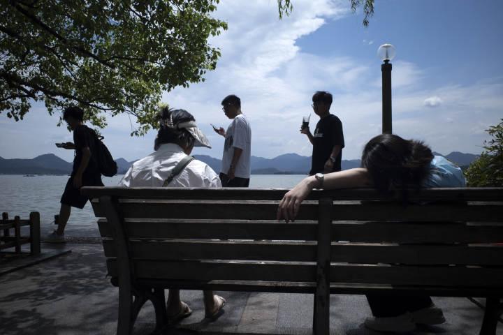蓝天白云下,西湖边玩累的游客。郑展.jpg
