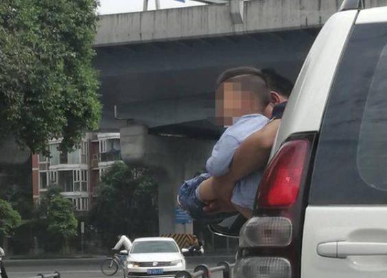 公路正在行驶的车上,男孩被抱出车窗外撒尿