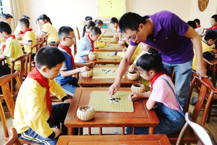 学生们在教师指导孩子们专心致志对弈.jpg